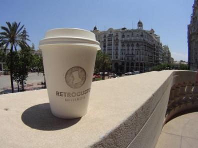Vaso de papel con logo de Retrogusto Coffeemates en el balcón del Ayuntamiento de Valencia